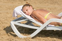Young tanned woman lying on a deck chair with his eyes closed on the beach.
