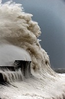 Huge waves crash against the harbour wall at Porthcawl, Bridgend, Wales, UK.