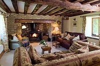 A cosy cottage living room with a log burning stove exposed stone walls and ceiling beams features. Editorial Use Only.