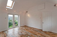 A large new unoccupied white painted high ceilinged empty room with Velux skylights.