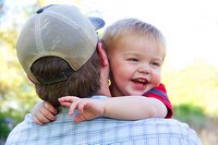 A man holding his young son outdoors in Spokane, Washington, USA.