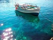 Vasiliki, Island of Lefkas, Greece. A boat in the clear sea along the coast.