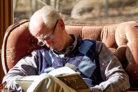 older man in glasses falling asleep in armchair in sunshine while reading, Monroe County, Indiana.