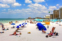 People enjoying the sunshine on Clearwater beach Florida, voted the number one beach in America.