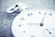 Pocket watch in close up lying on stone table. Vintage timepiece still life. Concept of time, deadline and nostalgia.