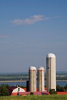 Red and white dairy farm with three grain silos in summer, Saint-Jean, Ile d´Orleans, Quebec, Canada.