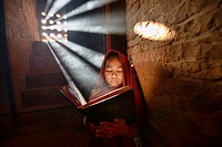 A young monk reading with rays of sunlight in the temples of Bagan, Myanmar.