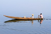 Fisherman on Hue river in traditional wooden canoe, Hue, Vietnam, Asia.