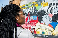New York City, USA. Attractive African-American woman looking at a graffiti about civil rights on a building´s wall, somewhere in Harlem, Manhattan.