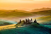 Val d´Orcia, Tuscany, Italy. A lonely farmhouse with cypress and olive trees, rolling hills.