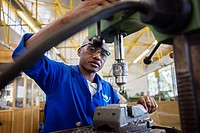 Fitting and Turning Trade of the Windhoek Vocational Training Centre, Namibia. Student works with a drill machine making holes through a piece of stee...