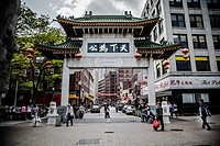 China Town in Boston, MA, USA with its Asian style portal surrounded by Chinese immigrants.