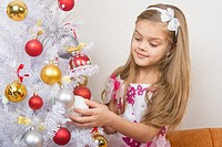 Seven-year girl in a beautiful dress treats Christmas toys.