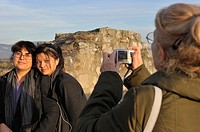 Grandmother taking photo of her granddaughter and daughter outdoors at a tourist destination.