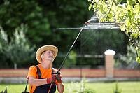 Russia. Belgorod region. Elderly man working in the garden. Processing of trees from pests.