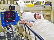 Mature woman in hospital bed attached to monitoring equipment.