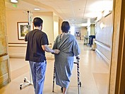 A hospital patient takes her first hallway walk assisted by a physical therapist just 5-hours following a knee replacement surgery. (Only the patient ...
