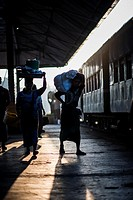 Silhouette of people carrying luggage waiting for the train departure at the Yangon Central Train Station, Myanmar.