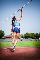 young sportswoman throwing javelin on an athletic piste