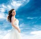 A smiling young blond woman dressed as a bride in front of a blue sky with clouds. Memphis, Tennessee, USA