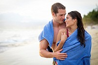 Young couple sharing a towel at a beach at Riviera Nayarit, Mexico.