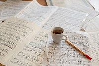 Strong coffee and music score on musicians desk.