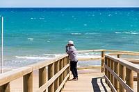 Guardamar del Segura beach Alicante Spain. Tourist man in Sand dune stabilization walkway.