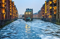 View of historic red brick warehouses with frozen canals in winter at Speicherstadt beside canals in Hamburg Germany.