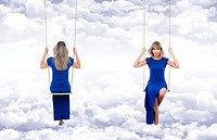 Smiling and relaxed blonde woman, front and back view, wearing a long blue dress on the swing, suspended through the clouds of a fantasy blue sky.