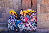 Three Peruvian girls posing with a western tourist in the city of Cusco.