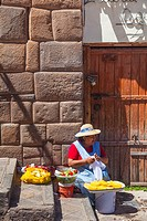 Woman selling Pineapple, Salad, and Potatoes on a Cusco sidewalk.