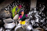 Women workers working in a silver cooking pot factory in Dhaka. Children as young as teen operate heavy machinery unaided, their faces, chest and arms...