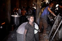 Portrait a Bnagladeshi child labor who work in a silver cooking pot factory in Dhaka. Children as young as teen operate heavy machinery unaided, their...