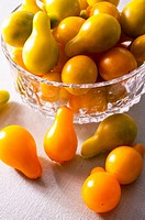A close up of a bunch of Yellow Pear tomatoes in a bowl and a table.