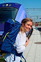 Young woman walks along a train on a railway platform in Ystad, Scania, Sweden.