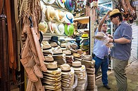 Salesman reacing to put a straw hat on a customer at a market in Oaxaca Mexico.