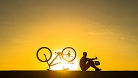 A mountain biker watches the sun rise over the Atlantic ocean from sea wall. Avenida Maritima, Las Palmas, Gran Canaria, Canary Islands, Spain. Europe...