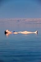 Young woman floating in the Dead Sea, Movenpick Resort Hotel, Jordan, Western Asia.