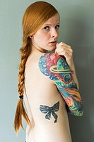 Tilburg, Netherlands. Studio portrait of a young, red haired woman with sleeve tattoo.