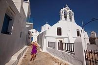 Woman near an Orthodox church in the old town Chora, Amorgos, Cyclades Islands, Greek Islands, Greece, Europe.