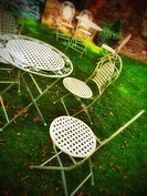 Metal chairs and tables on lawn England UK United Kingdom GB Great Britain.
