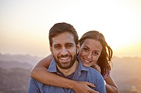 Happy young couple posing for a picture with a hazy mountainous background and happy smiles while wearing casual clothing.