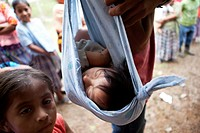 Chahal, Guatemala, a child from a Maya tribe in the jungle is being carried in cloth by her father. Her sister is watching.
