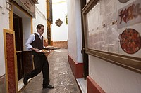 Sevilla, Spain, a waiter rushes from the kitchen to the other location to serve customers wih food.