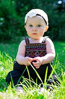 Baby girl at roughly 6 months old outdoors in a natural setting with available light for a lifestyle portrait.