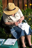 Mature woman knitting babyshawl for grandchild. UK.