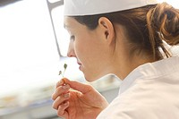 Chef sniffing leaves in restaurant kitchen