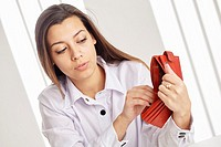 Young attractive woman searching money in the wallet.