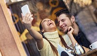 Laughing young couple making selfie in the cafe.