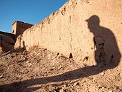 Visitor shadow on ruined wall in Ait Ben Haddou, Morocco.